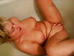 Mom in bathtub vibrates her pussy with water tubes