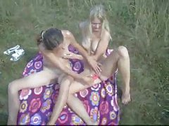 Lesbian couple playing lustily in the grass tubes