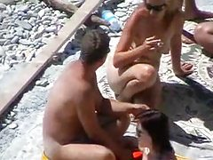 Two couples fool around on the beach tubes