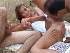 Two guys fuck a teen in a grassy field tubes