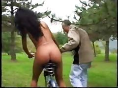 She rides a dildo bike in the grass tubes