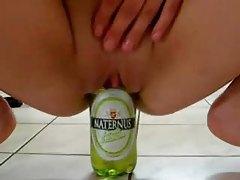 Amateur fucks a beer bottle in kitchen tubes