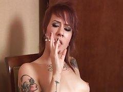 Heavily tattooed redhead smokes naked tubes