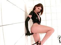 Leggy redhead in latex fucking her big black toy tubes