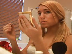 Pigtailed blonde puts on her makeup tubes