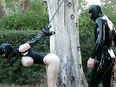 Latex slave smacked on the ass outdoors tubes