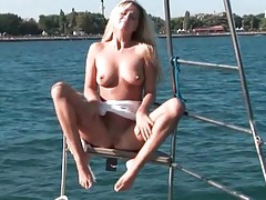 Blonde natural beauty poses on the boat tubes