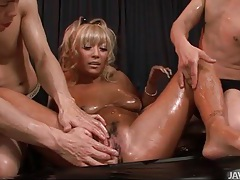 Tanned body soaked in oil and fondled tubes