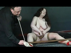 He unties her as she scrapes hot wax off tubes