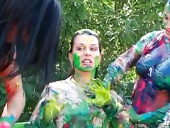 Girls spread body paint on each other outdoors tubes