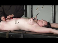 Bondage pulls on her tits as he does hot wax play tubes
