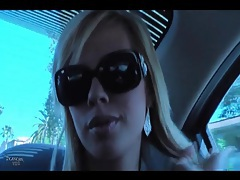 Pretty blonde in sunglasses chats in the car tubes