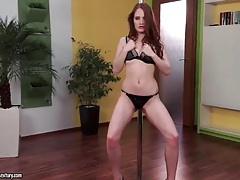 Redhead in short skirt works the pole tubes