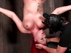 Redhead hangs upside down and takes a toy tubes