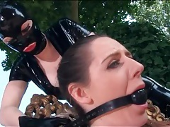 Latex femdom play outdoors with butt plug tubes