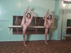 Two flexible ballerinas stretch in gym tubes