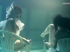 Pretty girls hold weights to stay underwater tubes