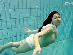 Girl in white panties swims in pool tubes