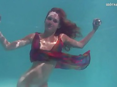 Young redhead swims in a pretty dress tubes