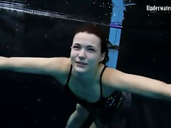 Beautiful girl swims and smiles underwater tube