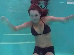 Redhead in cute bikini goes swimming tubes