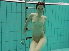 Talented swimmer is naked underwater tubes