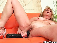 Grandmother with large breasts pushes huge dildo inside tubes