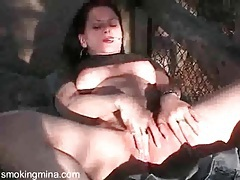 Brunette smokes and masturbates outdoors tubes