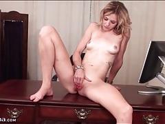 Naked blonde beauty masturbates on desk tubes