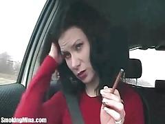 Brunette in the car smokes cigarette lustily tubes