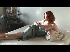 Redhead in a lovely satin dress smokes cigarette tubes