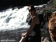 Redhead smokes by a waterfall in outdoor porn tubes