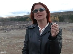 Redhead in a pretty leather coat smokes outdoors tubes