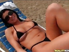 Romi rain models a skimpy bikini on the beach tubes