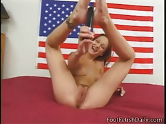 Redhead oils up her feet and plays with a dildo tubes