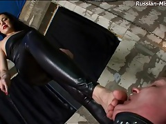 Mistress in tight leather has him suck her heels tubes