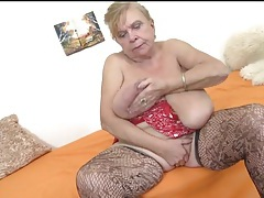 Granny sucks her tits and masturbates her cunt tubes
