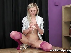 Blonde pees in wine glasses and pours it tubes