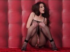 Leggy brunette in high heels and black fishnet lingerie tubes