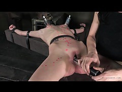 Gas mask and hot wax on babe in bondage tubes