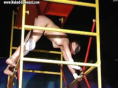Gymnast climbs the tower and bends her body tubes