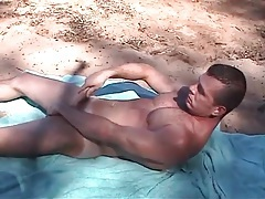 Muscular gay guy jerks off on a public beach tubes