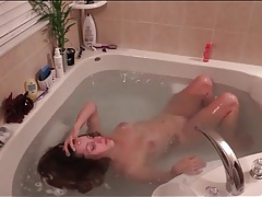 Brunette takes her time washing her hair in the tub tubes