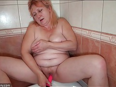 Pink haired granny pleasures her pussy in the shower tubes