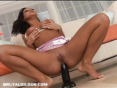 Tanned slut fills her asshole with a big black dildo tubes