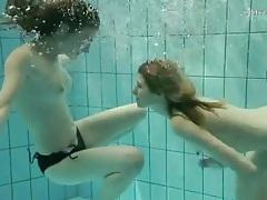 Underwater in the pool with cute teens in bikinis tubes