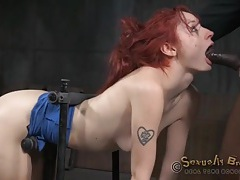 Slut strapped into a bondage device takes cock tubes
