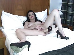 Sexy mature brunette sits on a long dildo tubes