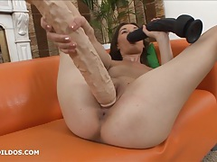 Hungry brunette sucks on a big dildo as the other fills her tubes