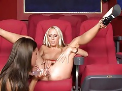 Lesbians in a home theater fuck their toys tubes